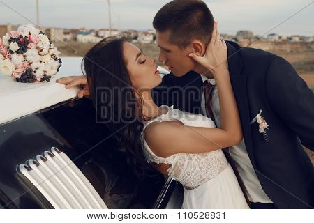 Beautiful Groom And Bride In Wedding Clothes Posing Beside A Car