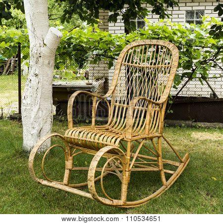Wicker Old Wooden Rocking Chair In The Garden