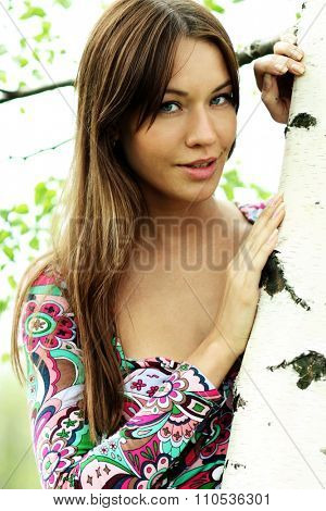 Portrait of the young beautiful woman on a background of leaves of a birch