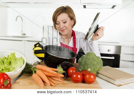Home Cook Woman In Red Apron At Domestic Kitchen Holding Cooking Pot With Hot Soup Smelling Vegetabl