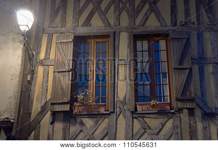 Lantern and timber-framed building windows at night