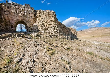 Stone Gate Of The Fortress With Crumbling Walls And Huge Bricks Of The Old Grungy Town In The Desert