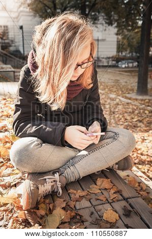 Cute Caucasian Blond Teenage Girl With Smart Phone