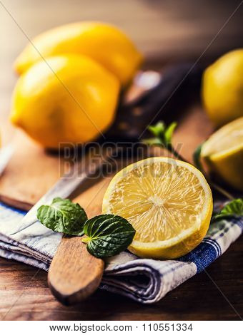 Lemons cut into the old kitchen board with mint leaves