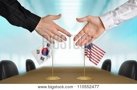 South Korea and United States diplomats shaking hands to agree deal