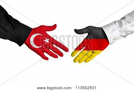 Turkey and Germany leaders shaking hands on a deal agreement