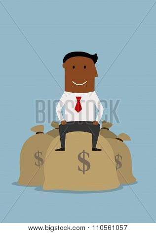 Happy smiling businessman on money bags