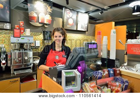 GENEVA, SWITZERLAND - NOVEMBER 18, 2015: barista in Starbucks Cafe. Starbucks Corporation is an American global coffee company and coffeehouse chain based in Seattle, Washington