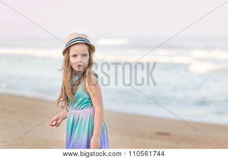 a little girl wearing a straw hat and a dress on a beach