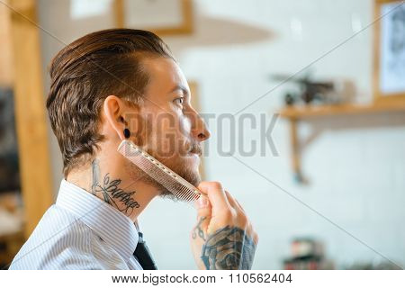 Professional barber brushing his beard