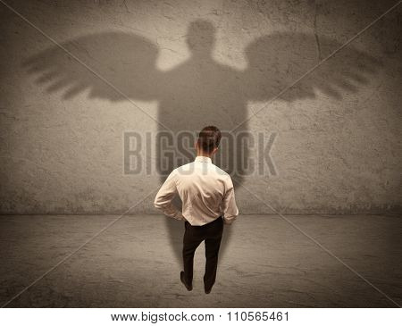 A successful businessman holding a briefcase is giving thumbs up for his angel shadow in front of a wall concept