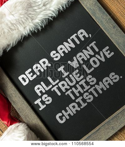 Dear Santa, All I Want Is True Love This Christmas written on blackboard with santa hat