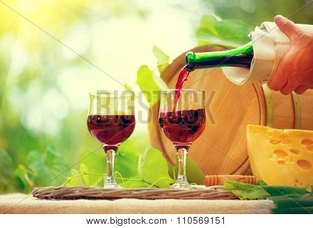Wine. Red wine and cheese. Romantic lunch outdoors. Pour white closeup over blurred nature green background