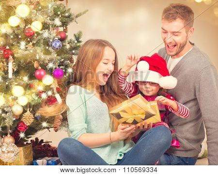 Christmas Family - Father, Mother and little child girl with holiday gifts box over Decorated Christmas tree, New Year Celebrating. Christmas Scene
