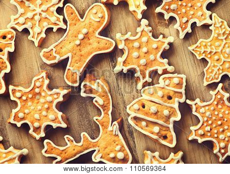 Christmas homemade cookies. Holiday Background with various Gingerbread cookies over wooden table. Traditional Christmas and New year food. Christmas decorated iced cookies on wood background