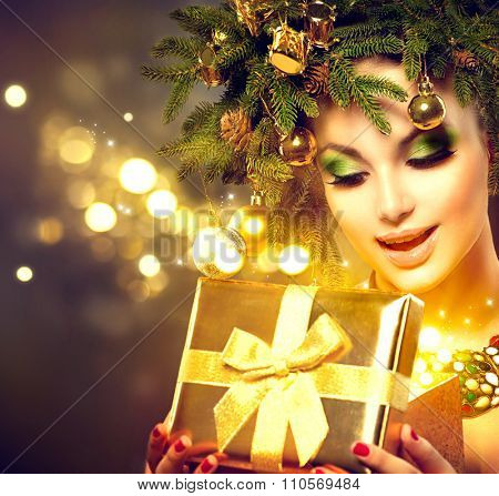 Christmas Winter Woman opening magic Christmas Gift box. Fairy. Beautiful New Year and Christmas Tree Holiday Hairstyle and Make up. Beauty Fashion Model Girl With Present Box. Holiday Magic stars
