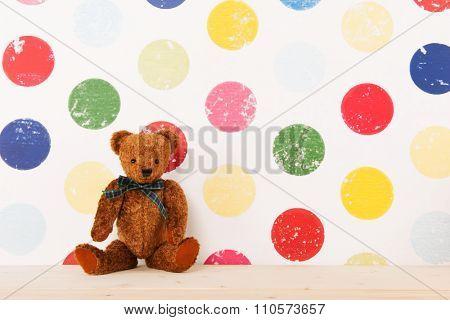 Old brown bear on shelve in nursery room