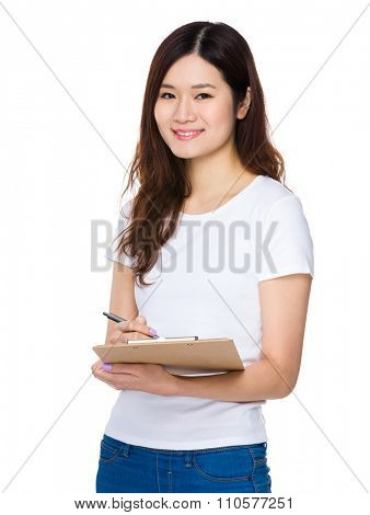 Asian woman jot down the note on clipboard