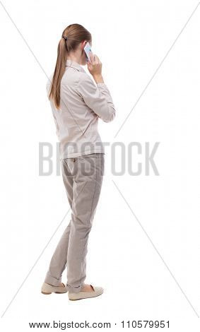 back view of a woman talking on the phone.  backside view of person.  Rear view people collection. Isolated over white background. A girl in a white jacket is pressed the phone to his ear.