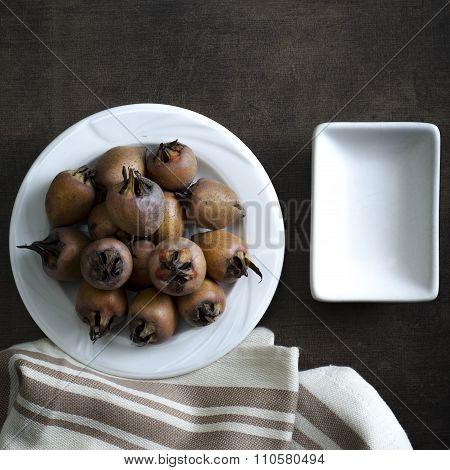 Ripe Medlar Fruit On White Plate On Wooden Table