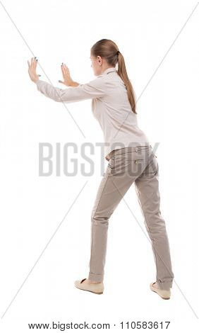 back view of woman pushes wall. Isolated over white background. Rear view people collection. backside view of person. Girl with long hair in a white jacket repelled