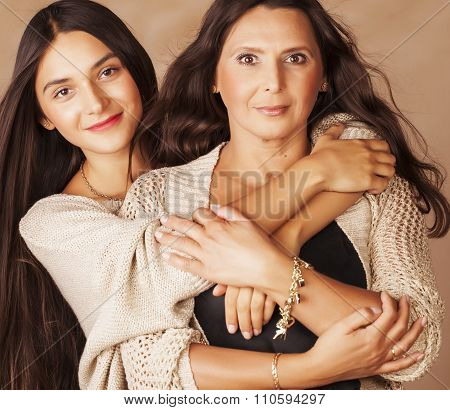 cute pretty teen daughter with mature mother hugging, fashion style brunette makeup close up tan