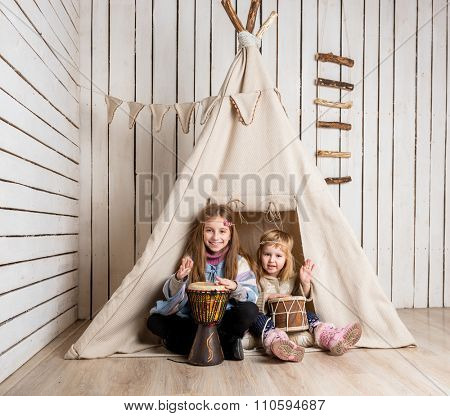 smiling little girls playing drums near wigwam like Indians
