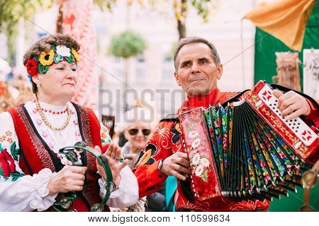Unknown man in national clothes plays the accordion folk Belarus