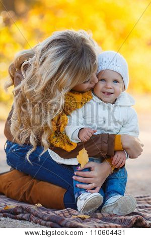 Woman and child playing and cuddling at autumn park.