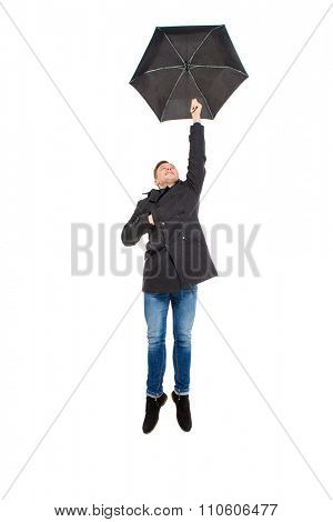 Attractive handsome young man in black coat and jeans flying with umbrella over white background