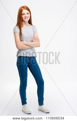 Young beautiful woman with long red hair standing with crossed arms over white background