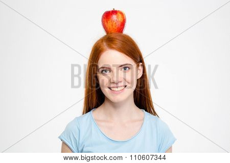 Portrait of a smiling redhead woman standing with apple on head isolated on a white backgroun