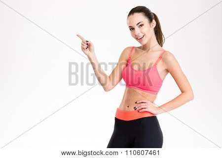 Cheerful attractive young fitness woman in pink top and black leggings pointing away isolated over white background