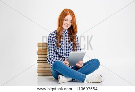 Happy beautiful young redhead curly woman using tablet and sitting with books behind her isolated over white background