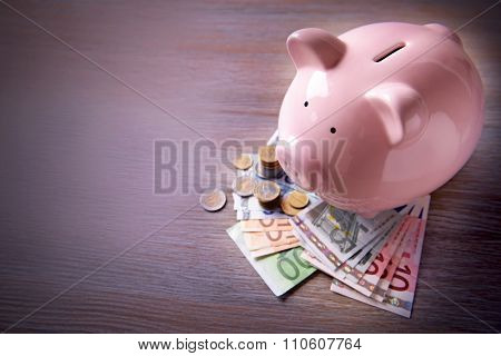 Pig moneybox with Euro banknotes and coins on wooden background