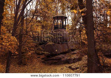 Arbour on big stones in the autumn park
