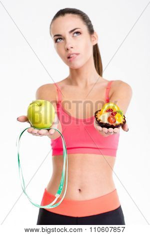 Thoughtful unsure fitness girl on diet holding apple, measuring tape and cake over white background