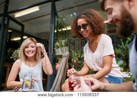 Small Group Of Friends Enjoying At Outdoor Cafe