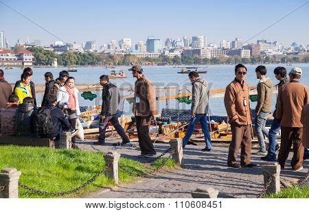 Tourists And Boatmen On West Lake Coast
