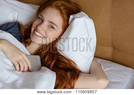 Portrait of a smiling redhead woman lying in the bed with smartphone and looking at camera