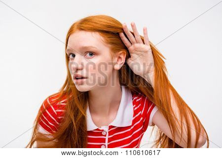 Curious young attractive female with beautiful long red hair in striped t-shirt trying to listen rumors