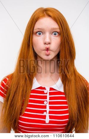 Funny amusing redhead girl fooling around and making funny faces over white background