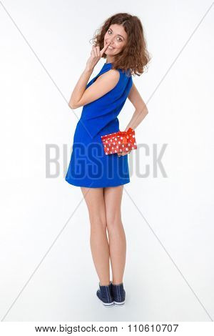 Full length portrait of a happy woman holding gift box and showing finger over lips isolated on a white background