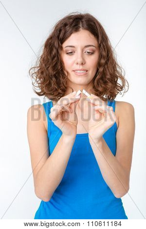 Portrait of a young woman braking cigarette isolated on a white background