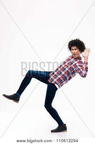 Full length portrait of afro american man falling isolated on a white background