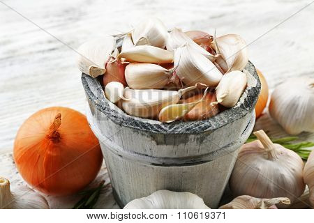 Composition of garlic, onion and rosemary on wooden table