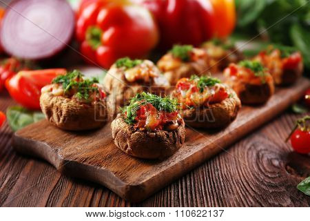 A wooden tablet with stuffed mushrooms and vegetables on the table