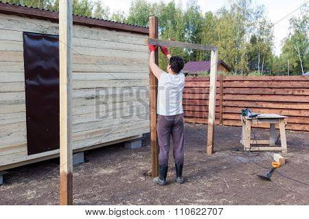 Man Measuring Wooden Post On The Level