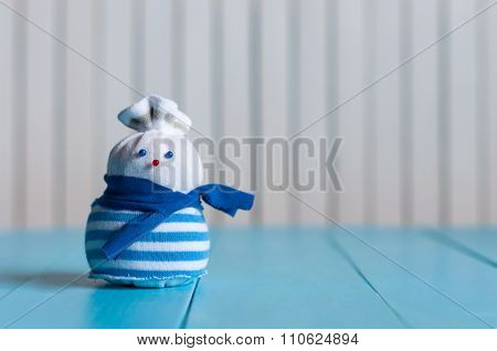 Funny little handmade snowman in a blue stripy sweater on wooden background. Christmas time, New yea