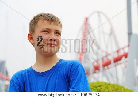 Portrait of a boy on the background of a roller coaster at an amusement park.  Drawing a dragon on her cheek.